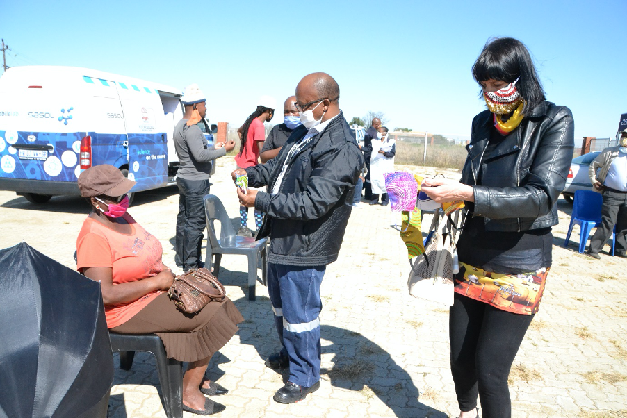 Rightwell Laxa, Senior Vice President: Sasolburg Operations with Esme Young, Community Affairs Ikusasa Manager, distributing cloth face masks to elderly community members in Sasolburg.
